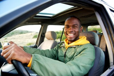 Naklejka smiling young african american man driving car