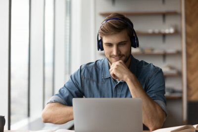 Naklejka Smiling young male student in headphones watch webinar on computer study online from home. Happy man in earphones learn work distant on laptop, talk on webcam zoom video call. Education concept.