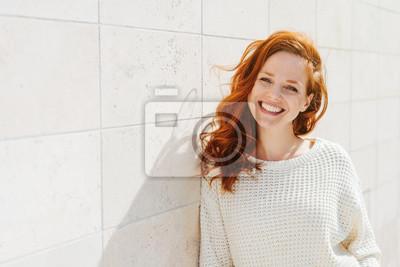 Naklejka Smiling young woman near white wall