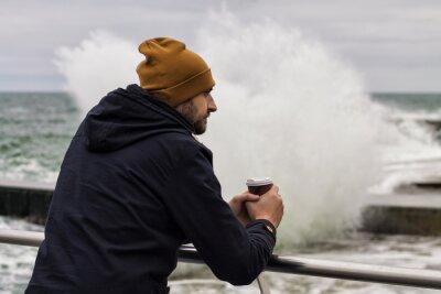 Naklejka Smutny człowiek rozgrzewa dłonie z filiżanką kawy na wynos. Sea Splash jest w tle, zimnie w zimie.