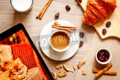 Naklejka śniadanie w domu na drewnianym stole z filiżanką kawy mleka, rogalików i tabletki