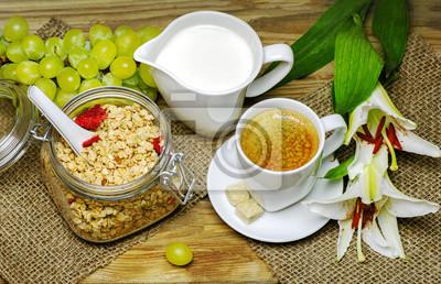 Naklejka Śniadanie z muesli, ciepłe mleko, świeże kiść winogron i filiżanką espresso umieszczonych z pięknym kwiatem lilii na tle drewnianych.