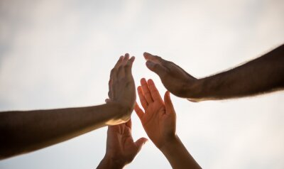 Naklejka Soft focus of people giving fist bump showing unity and teamwork. Friendship happiness leisure partnership team concept.