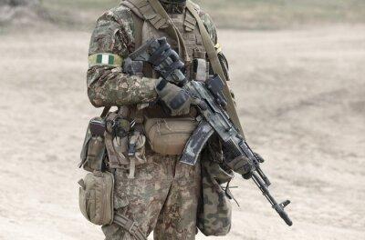 Naklejka Soldier with machine gun and flag of Nigeria on military uniform. Collage.