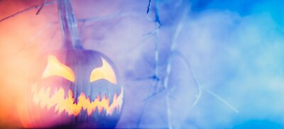 Naklejka Spooky Halloween jack o lantern pumpkin with carved scary face glowing in fog on Halloween night. Copy space for text.
