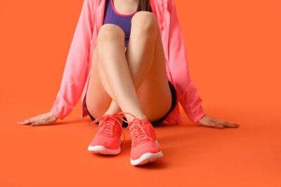 Naklejka Sporty young woman on color background