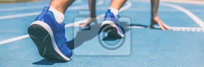 Naklejka Sprinter czeka na rozpoczęcie wyścigu na bieżni na zewnątrz stadionu. Sport i fitness biegacz człowiek sportowiec na niebiesko uruchomić utwór z buty do biegania. Panorama baneru.