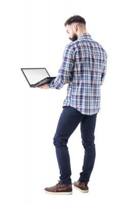 Naklejka Stały człowiek działalności zawodowej gospodarstwa i przy użyciu komputera przenośnego z pustym ekranem. Pełny ciało odizolowywający na białym tle.