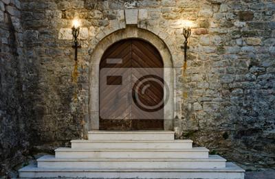 Naklejka Stare drewniane drzwi starożytnego zamku z białymi schodami są oświetlone płonącymi pochodniami.