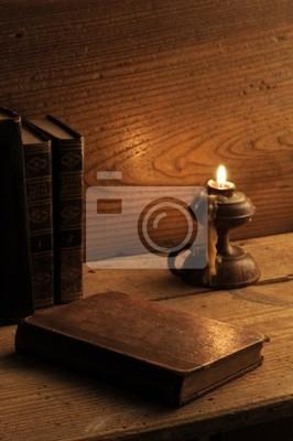Naklejka stare książki na drewnianym stole, przy świecach