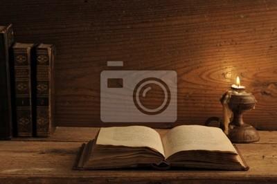 stare książki na drewnianym stole, przy świecach