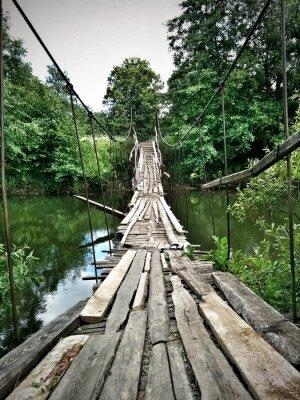 Naklejka Stary pół-zniszczony drewniany most nad niewielką rzeką