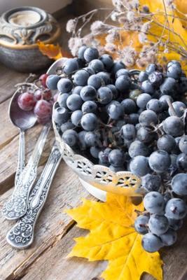 Stary srebny naczynie z winogronami, łyżki, jesień liście na drewnianym tle
