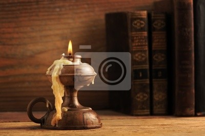 stary świeca na drewnianym stole, stare książki w tle