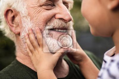 Naklejka Stary uśmiechnięty mężczyzna i jego wnuczka, patrząc na siebie