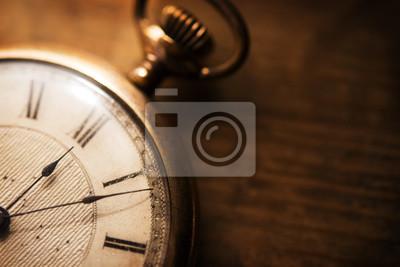 Naklejka Stary zegarek kieszonkowy na grungy drewniane biurko. Strzał w niskim tonie i niezwykle płytka głębia dla wrażenia wrażenia. Skupiamy się na wytrawianiu tarczy zegara.