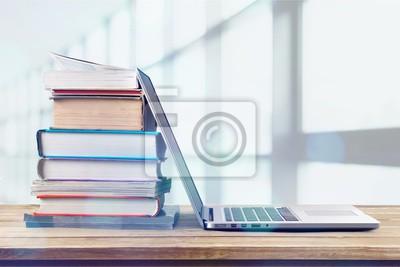 Naklejka Sterta książki z laptopem na drewnianym stole