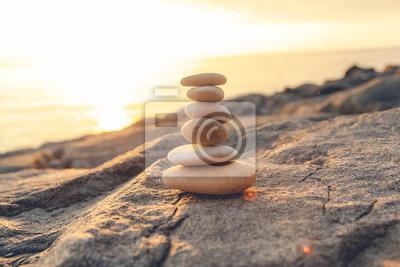 Naklejka Stones pyramid on the seashore at sunset