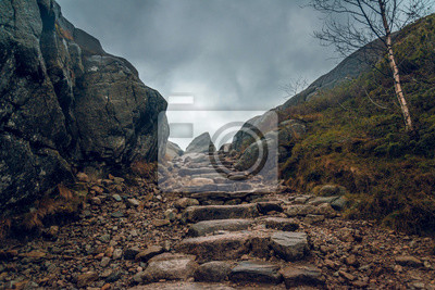Naklejka Stony path through the cliffs. Stony hiking trail in the mountains.