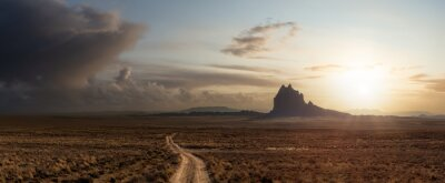 Naklejka Striking panoramic landscape view of a dirt road in the dry desert with a mountain peak in the background. Colorful Sunset Sky Art Render. Taken at Shiprock, New Mexico, United States.