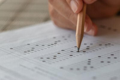 Naklejka Student hand testing doing test exam with pencil drawing selected choices on answer sheet in school final exams at college or university. Taking multiple choice for assessment in examination classroom