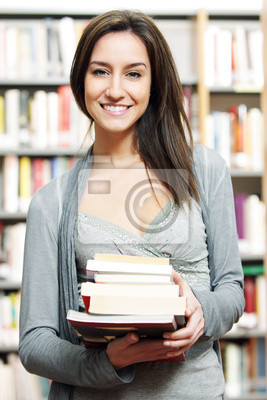 student with pile of books in the Library