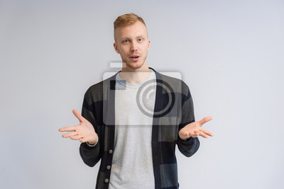 Naklejka Studio portrait concept of a smiling young man talking on a white background.