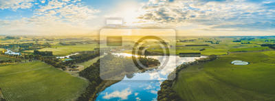 Naklejka Sun setting over scenic Australian countryside grasslands and pastures with river passing through - aerial panorama