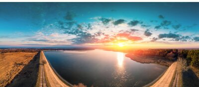 Sunrise over lake in early spring. Serene lake in the morning. Nature landscape. Dam on the lake. View from above. Panorama