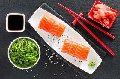 Naklejka sushi i zielone wodorosty sałatki na stole łupków