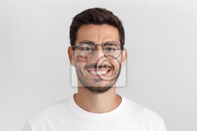 Naklejka Światło dzienne portret młody przystojny mężczyzna kaukaski na białym tle na szarym tle, ubrany w białą koszulkę i okrągłe okulary, patrząc na kamery i uśmiechając się pozytywnie