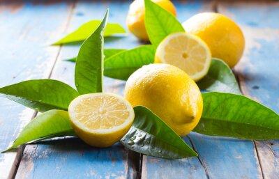 Naklejka Świeże cytryny z liśćmi na niebieskim tle starych drewnianych