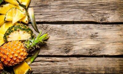 Naklejka Świeże plastry ananasa w całości. Na drewnianym tle.