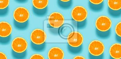 Naklejka Świeże połówki pomarańczy na niebieskim tle