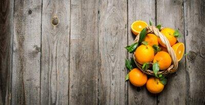 Naklejka Świeże pomarańcze w koszu z liśćmi.