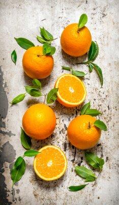 Naklejka Świeże pomarańcze z liśćmi. Na tle tamtejsze.