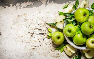 Naklejka Świeże zielone jabłka w naczyniu na rustykalnym tle.