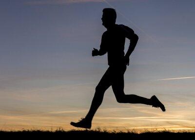 Naklejka Sylwetka biegacza w zachodzie słońca