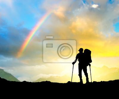 Sylwetka turysta na szczycie góry.