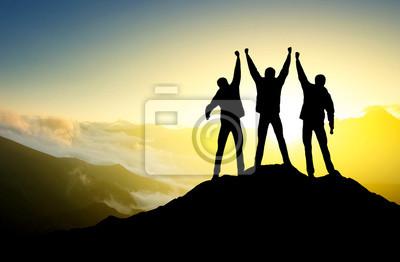Sylwetka zespołu na szczycie góry.