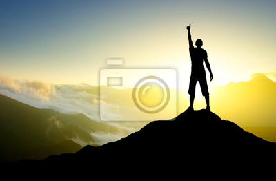 Sylwetka zwycięzcy na szczycie góry.