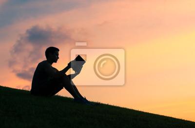 Naklejka Sylwetki młodego człowieka czytającego książkę.