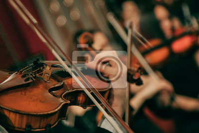 Naklejka Symphony orchestra on stage, hands playing violin. Shallow depth of field, vintage style.