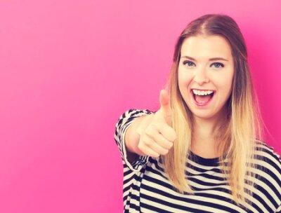 Naklejka Szczęśliwa młoda kobieta daje kciukowi up na różowym tle