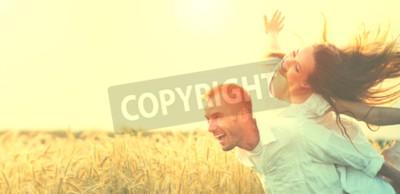 Naklejka Szczęśliwa para ma zabawę outdoors na pszenicznym polu nad zmierzchem