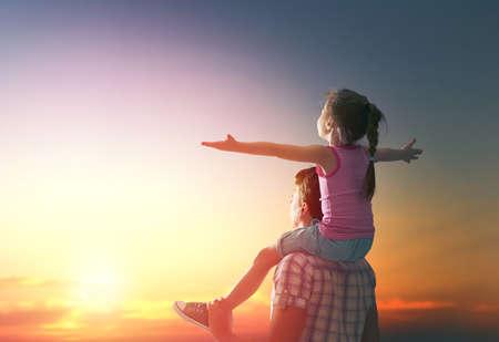 Naklejka szczęśliwa rodzina o zachodzie słońca. ojciec i córka zabawy i zabawy w przyrodzie. dziecko siedzi na ramionach ojca.