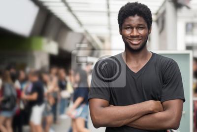 Naklejka szczęśliwy afrykański mężczyzna; portret szczęśliwy uśmiechający się pewnie młody dorosły czarna skóra afrykańskiego człowieka w stroju casual, miejski miejski scena na zewnątrz; model mężczyzna młody