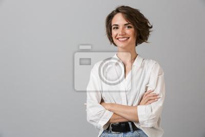 Naklejka Szczęśliwy młody biznes kobieta pozowanie na białym tle na szarym tle ściany.