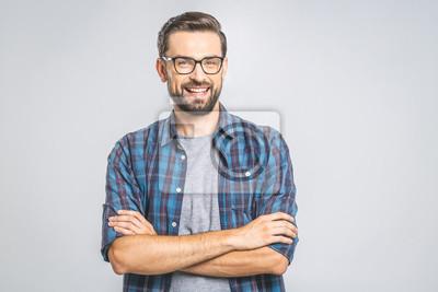 Naklejka Szczęśliwy młody człowiek. Portret przystojny młody człowiek utrzymuje ręki krzyżować i ono uśmiecha się w przypadkowej koszula podczas gdy stojący przeciw popielatemu tłu