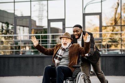 Naklejka szczęśliwy senior niepełnosprawny mężczyzna na wózku inwalidzkim i mężczyzna african american zabawy podczas jazdy ulicą
